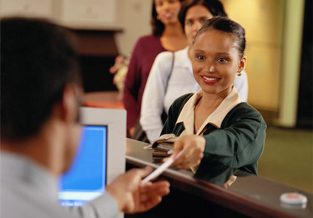 Personal banker is taking an ID card from a young lady, ready to process their transaction