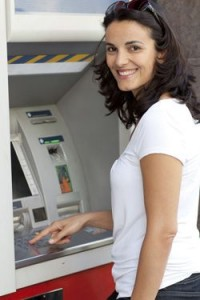 Smiling lady is withdrawing money from ATM