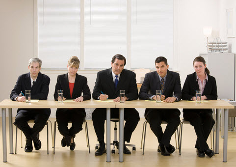 A tough interviewing panel waiting for personal banker job candidates. Two women and three men, all in black jackets